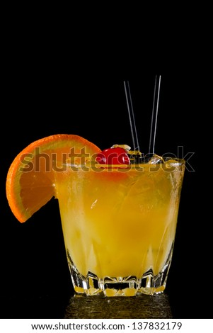 whiskey sour cocktail served on the rocks isolated on a black background garnished with an orange slice and a maraschino cherry - stock photo