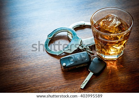 Whiskey with car keys and handcuffs concept for drinking and driving - stock photo