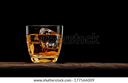 Whiskey with ice cubes in rocks glass on log table - stock photo