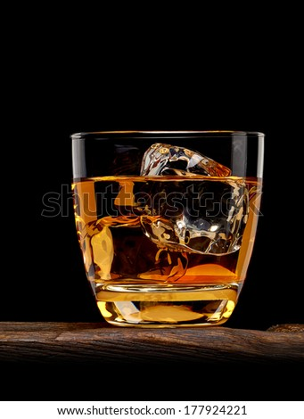 Whiskey with ice cubes in rocks glass on wooden table