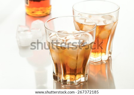 whiskey with ice in glass glasses - stock photo