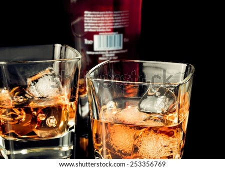 whiskey with ice in glass on black background near bottle, with reflection - stock photo