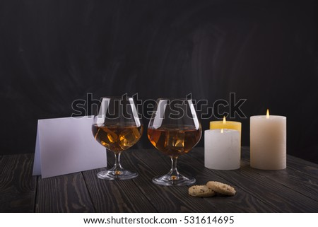 Whiskey with ice in glass on wood background. Romantic evening with candle. Love confession. Cognac, brandy, liquor, scotch in glass.