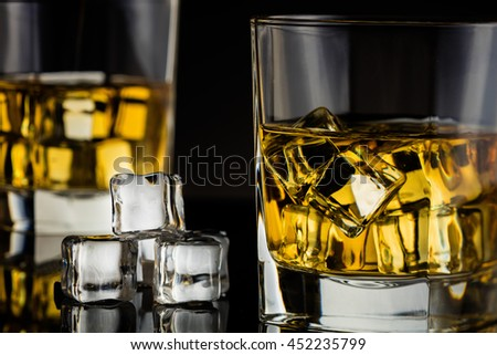 whiskey with ice on a black background