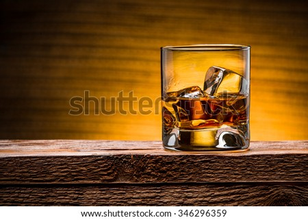 whiskey with ice on a wooden table - stock photo