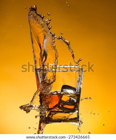 Whiskey with ice with liquid splash, freeze motion. - stock photo