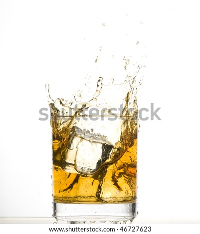 Whisky and ice. Brown brandy with splashing - stock photo