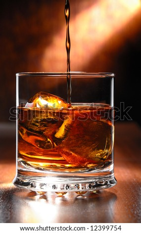 whisky beeing poured into a glass - stock photo