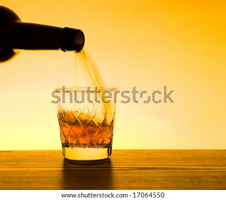Whisky being poured into glass - stock photo