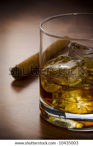 Whisky glass with havanna cigar on the table - stock photo