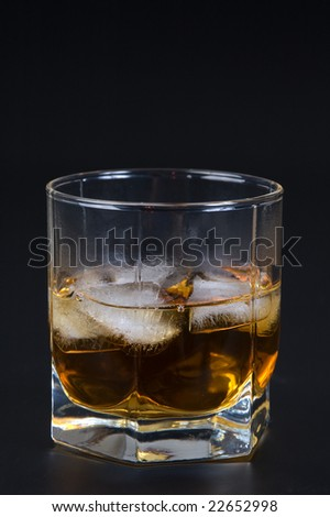 Whisky in a glass with ice against a dark background