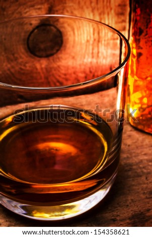 Whisky Scotch in a glass and a bottle on old wooden table. Old vintage oak countertop and glass of hard alcohol.Close up.  - stock photo
