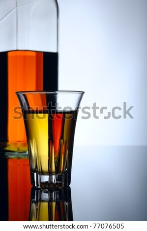 Whisky shot and bottle on a black reflective surface