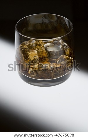 Whisky  with ice on creative black background