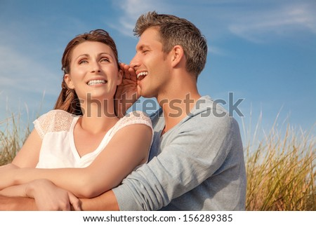 whispering couple in golden field on sunset
