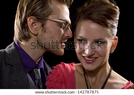 whispering couple on black background - stock photo