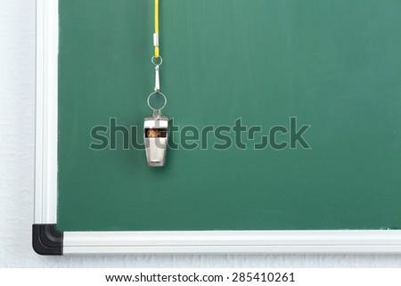 Whistle on blackboard background - stock photo