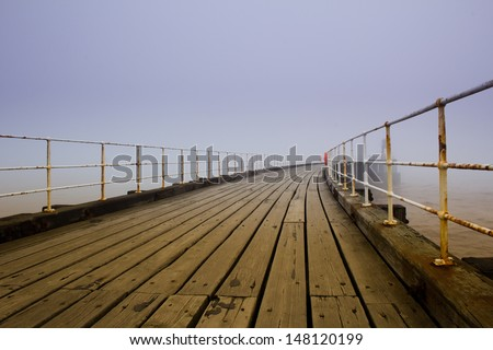 Whitby pier in fog - stock photo