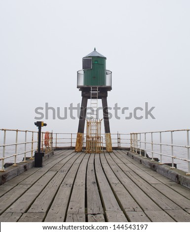 Whitby West Pier and Harbour in thick fog. Yorkshire, England.
