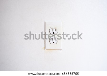 White AC power outlet on white wall