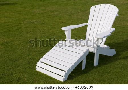 White adirondack lounge chair in green grass - stock photo