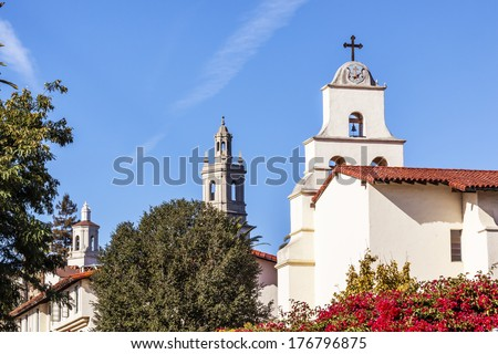 White Adobe Cross Steeples Bell Mission Red Bougainvillea Santa Barbara California.  Founded in 1786 at the end of Father Junipero Serra life. - stock photo