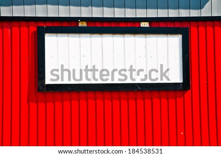 White advertisement panel on a red wall - stock photo