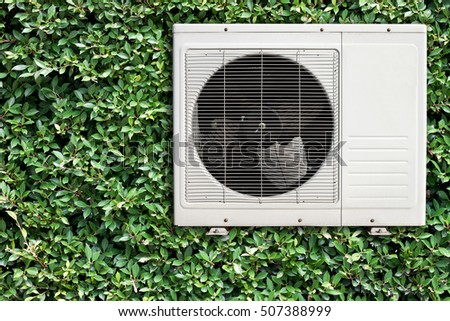White air conditioner compressor on natural green wall.