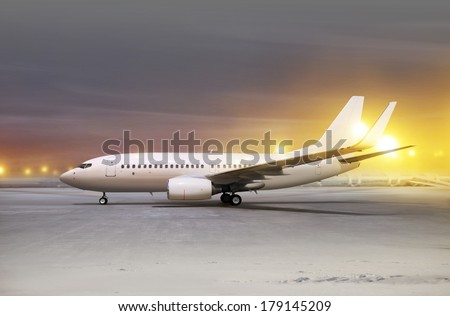 white aircraft in airport at non-flying weather, blowing snow  - stock photo