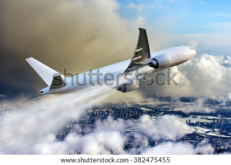 White aircraft in the sky. The plane flies over foggy and smoky industrial city. - stock photo