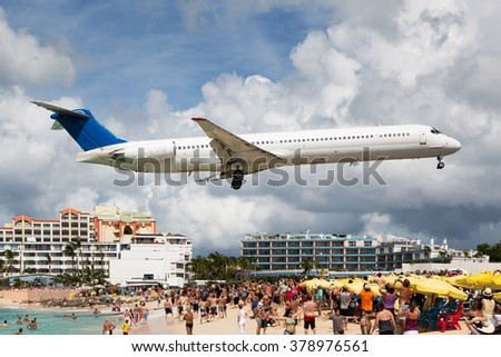 White aircraft with blue tail landing near the beach and swimming people - stock photo