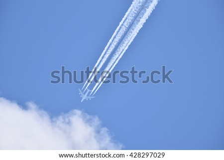 White airliner transports passengers while it pulling white contrails in blue cloudy sky - stock photo