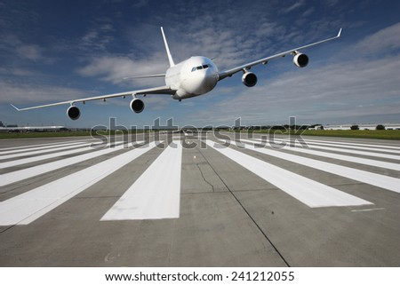 White airplane overflights low over the runway threshold - stock photo