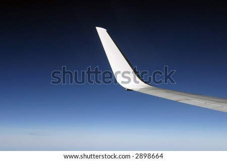 White airplane wing on dark blue sky