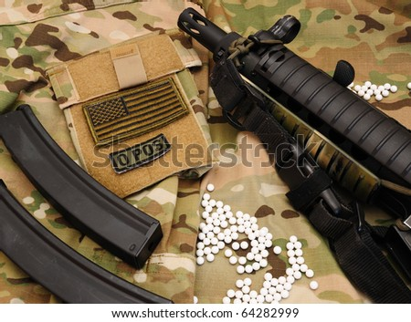 White airsoft bullets and sub-machine gun on multicam background