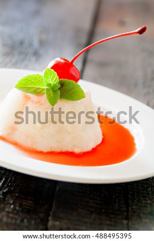 White airy cream-mousse dessert with syrup, cherry, mint on dark wooden background.