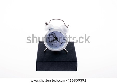 White alarm clock on a black box