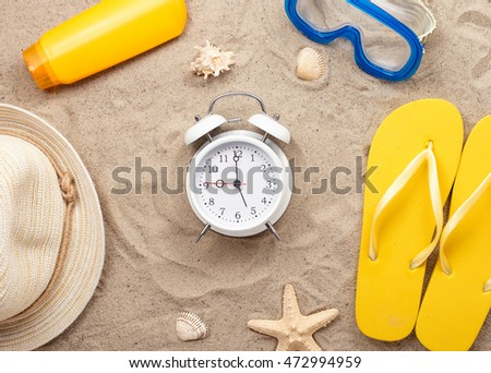 White alarm clock with beach items on sand, top view. Summer background