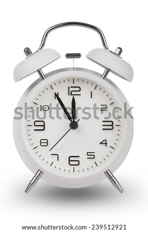 White alarm clock with the hands at 5 minutes till 12. Illustrating Time is Running Out isolated on a white background - stock photo