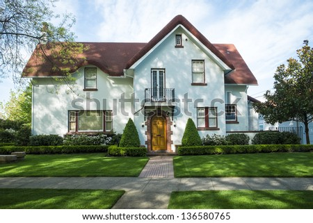 White American craftsman stucco house with a red roof - stock photo