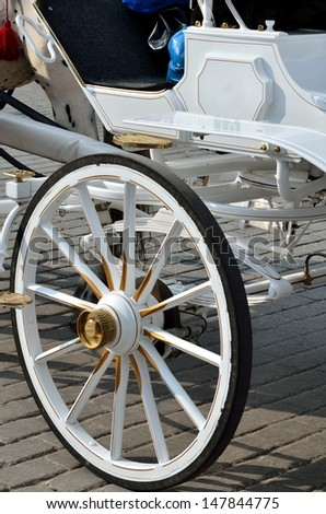 White ancient wheel and cab in krakow poland - stock photo