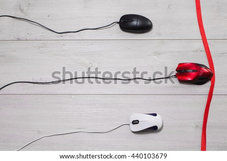 White and black, and red computer mouse on a white wooden background. Competition in the business, red tape. - stock photo