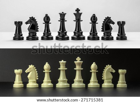 White and Black chess figures isolated on black and white background. Black and White Chess pieces are lined up. Set of chess figures. - stock photo