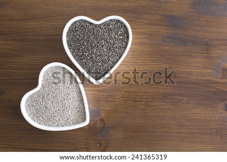 White and black chia seeds in heart shaped containers iwth room for copy - stock photo