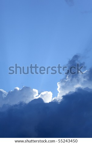 White and black clouds on blue sky  with sun beams - stock photo