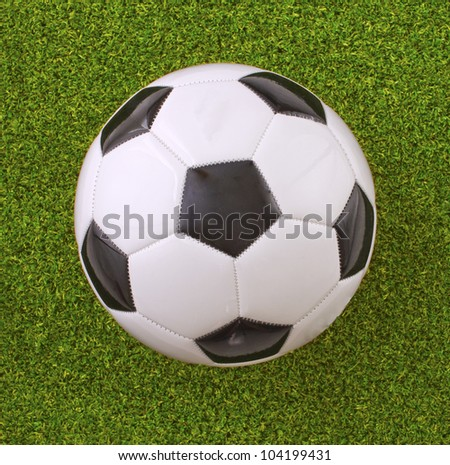 White and black football over the grass - stock photo