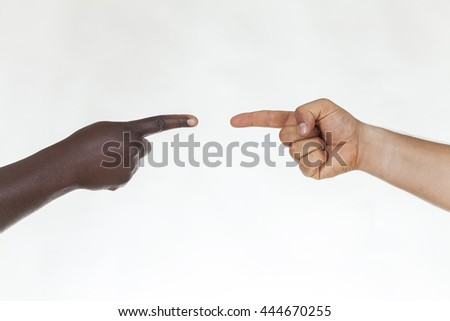 White and black hands touching their index fingers. Interracial concept - stock photo