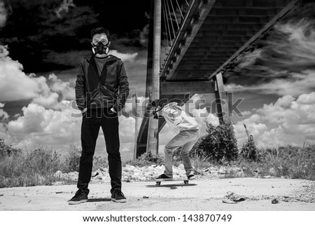 White-and-black image of young guys in gas-masks outside - stock photo
