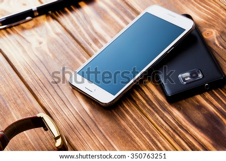 white and black mobile phones on the wooden background - stock photo