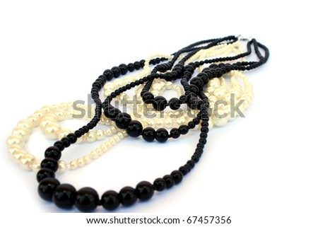 White and black necklaces isolated on white background. - stock photo